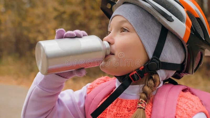 Het jonge geitje drinkt water van een aluminiumfles Één Kaukasische de fietsweg van kinderenritten in de herfstpark Meisje berijd stock foto