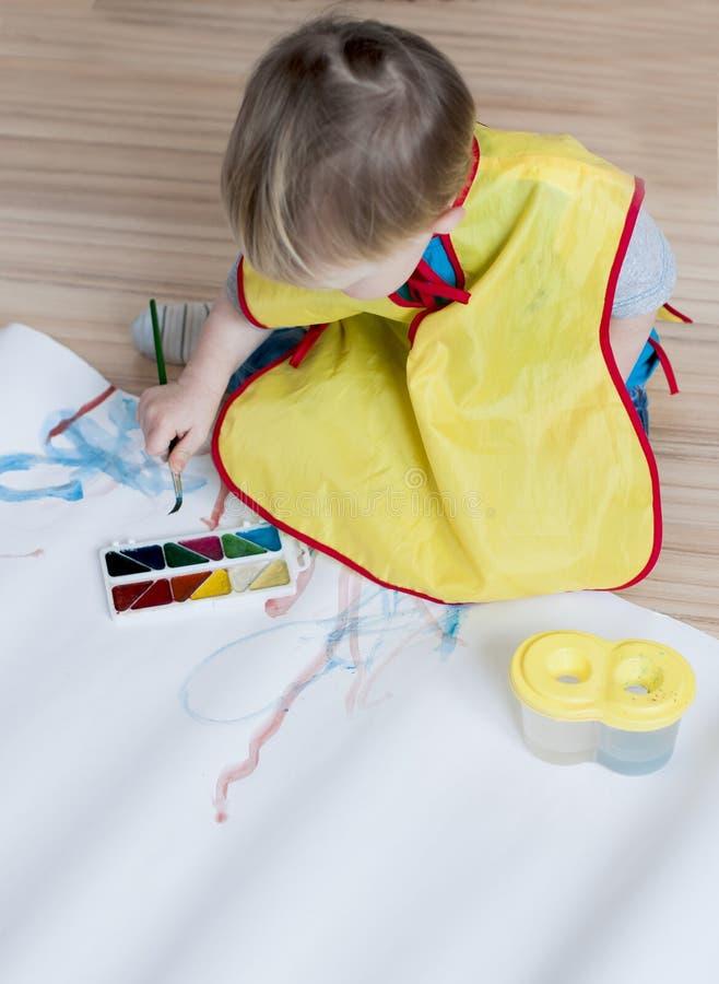 Het jonge geitje in een geel vest trekt een borstel op een Witboekverstand stock afbeeldingen