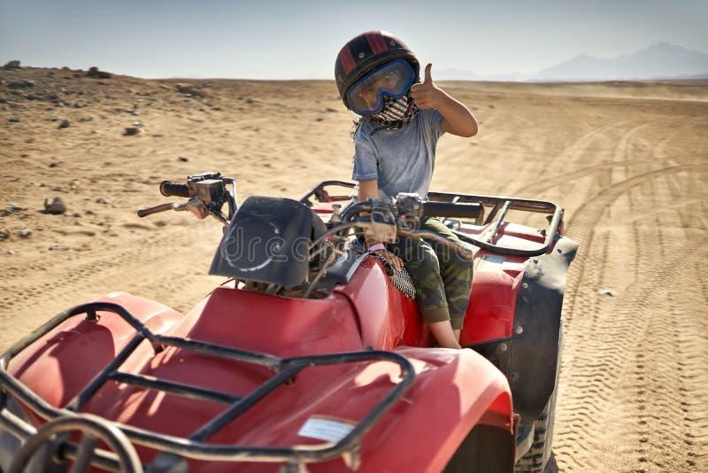 Het jonge geitje in helm en beschermt fiets van de masker de berijdende vierling royalty-vrije stock foto's