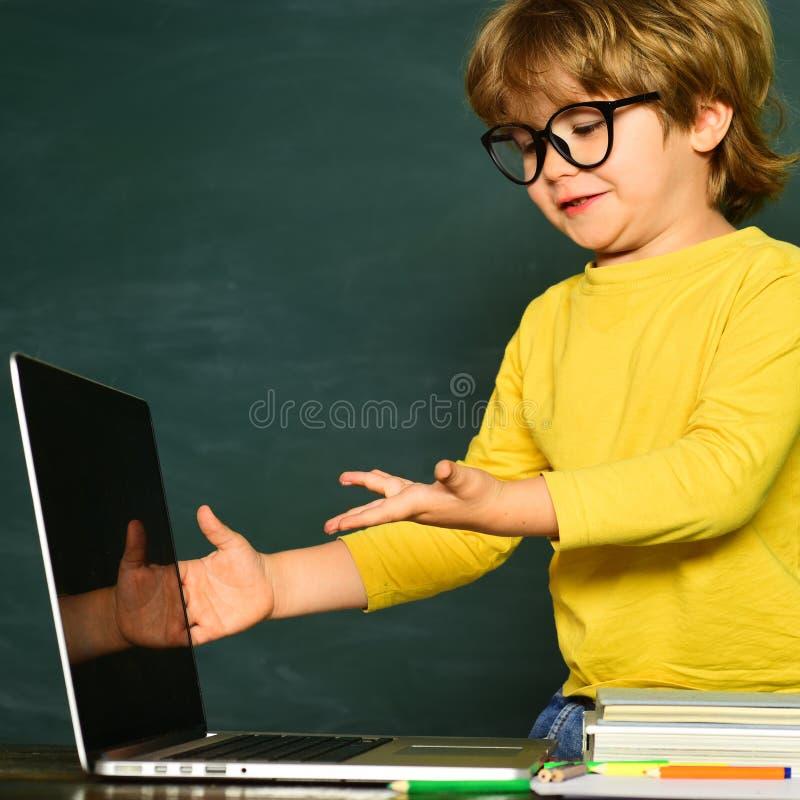 Het jonge geitje leert in klasse op achtergrond van bord Het concept van het wetenschapsonderwijs Leuk weinig peuterjong geitjejo stock foto