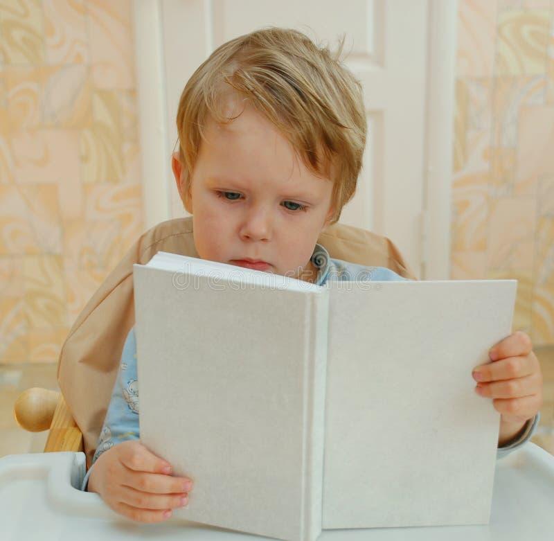 Het jonge geitje leest het boek stock afbeelding