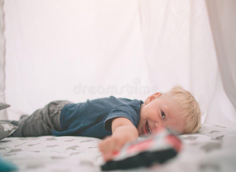 Het jonge geitje legt op de vloer De jongen speelt in huis met stuk speelgoed auto's thuis in de ochtend Toevallige levensstijl i stock foto