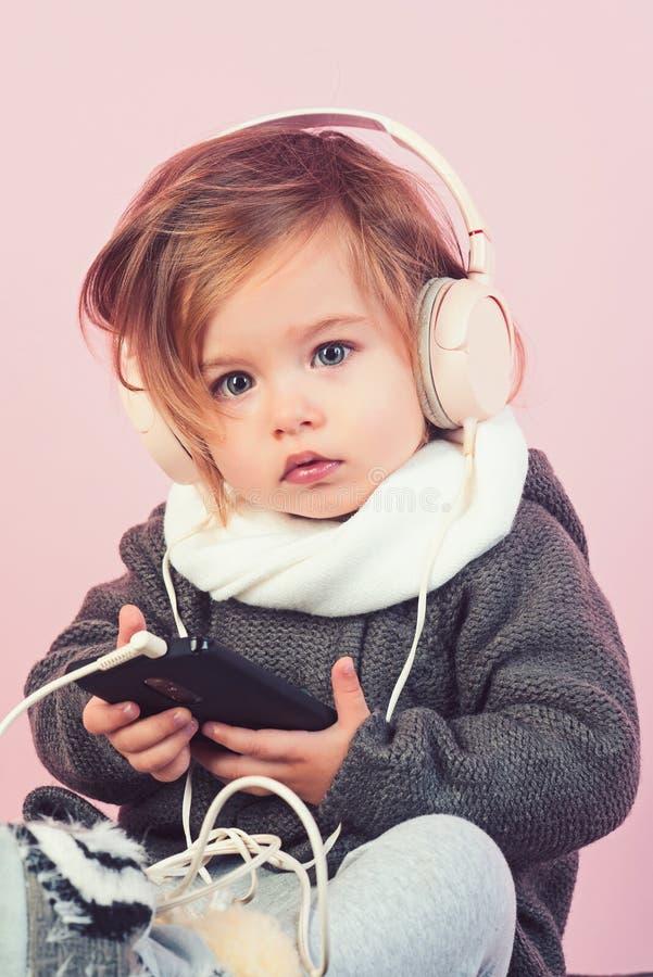 het jonge geitje luistert muziek met hoofdtelefoon en mp3 op telefoon Het hebben van pret de manier van het de winterjonge geitje stock foto's