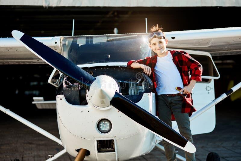 Het jonge geitje met schroevedraaier bevindt zich dichtbij single-engine propellervliegtuigen royalty-vrije stock foto's