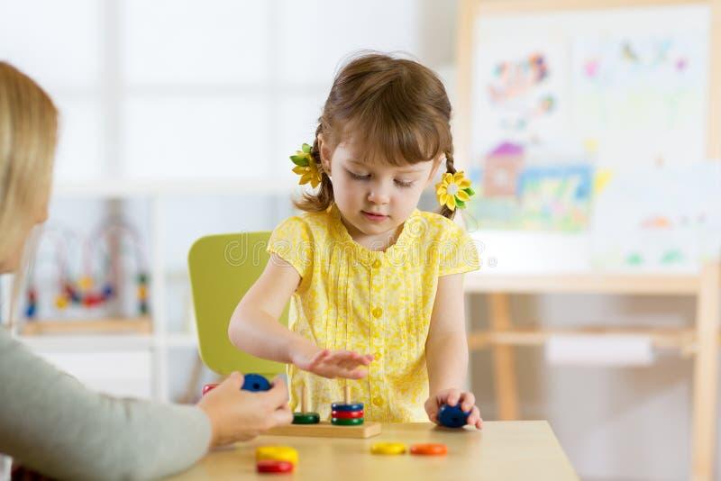 Het jonge geitje speelt met speelgoed in kinderdagverblijf stock foto's