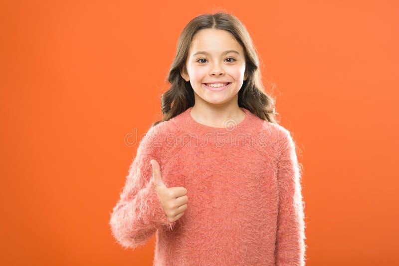 Het jonge geitje toont duim Gelukkige het meisje adviseert hoogst Hoog - kwaliteitsproduct Tevreden klant Duim op middelentevrede stock foto