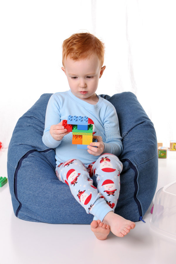 Het jonge geitje van de pyjama op beanbag stock foto's