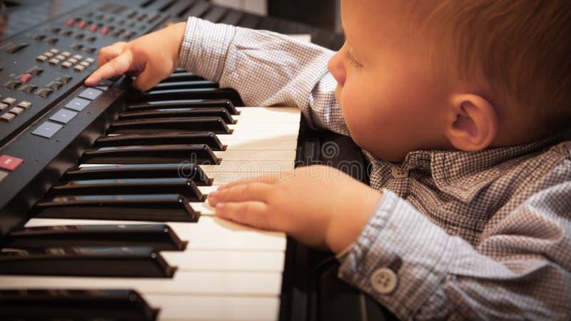 Het jonge geitje van het jongenskind het spelen op de digitale synthesizer van de toetsenbordpiano stock foto