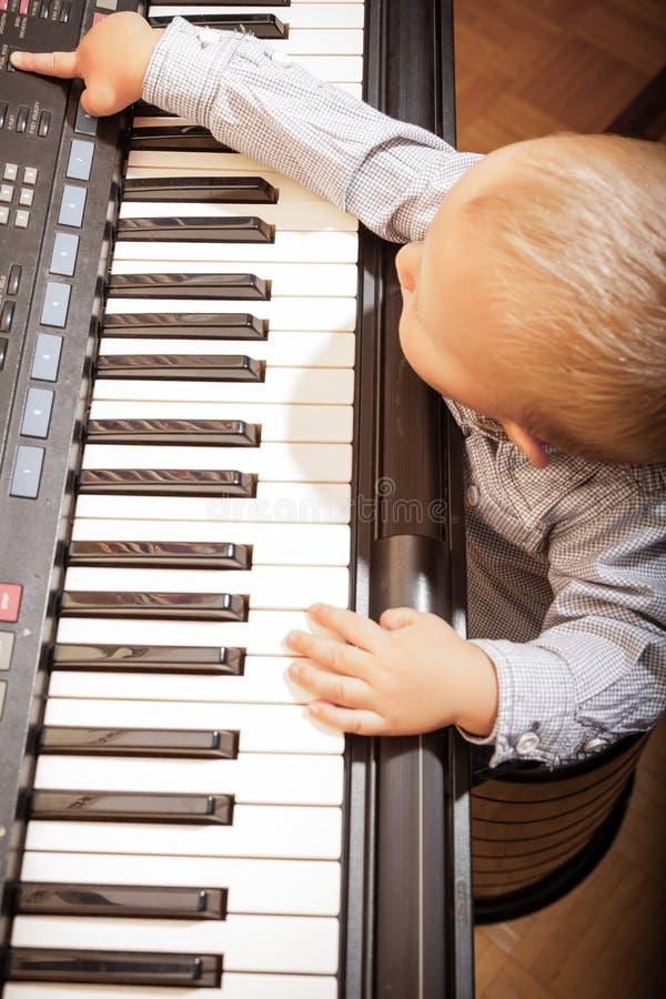 Het jonge geitje van het jongenskind het spelen op de digitale synthesizer van de toetsenbordpiano royalty-vrije stock fotografie