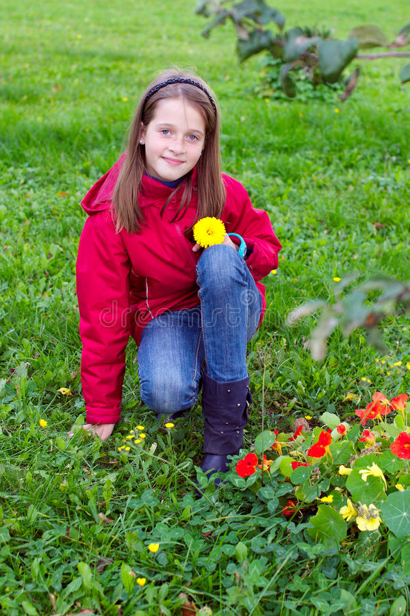Het jonge geitje van het meisje het stellen met een bloem in een weide stock afbeelding