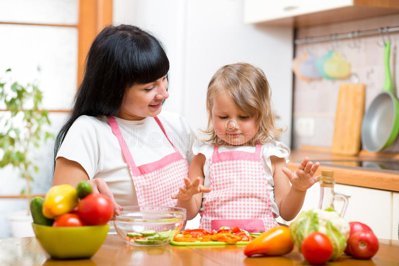 Het jonge geitjedochter die van het moederonderwijs salade voorbereiden bij keuken stock afbeelding