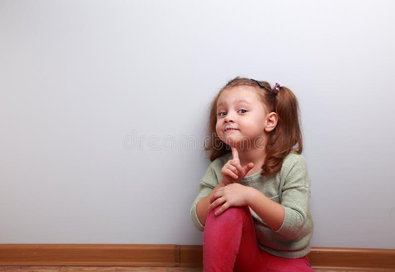 Het jonge geitjemeisje die van de pret glimlachend zitting met vinger dichtbij gezicht denken royalty-vrije stock fotografie