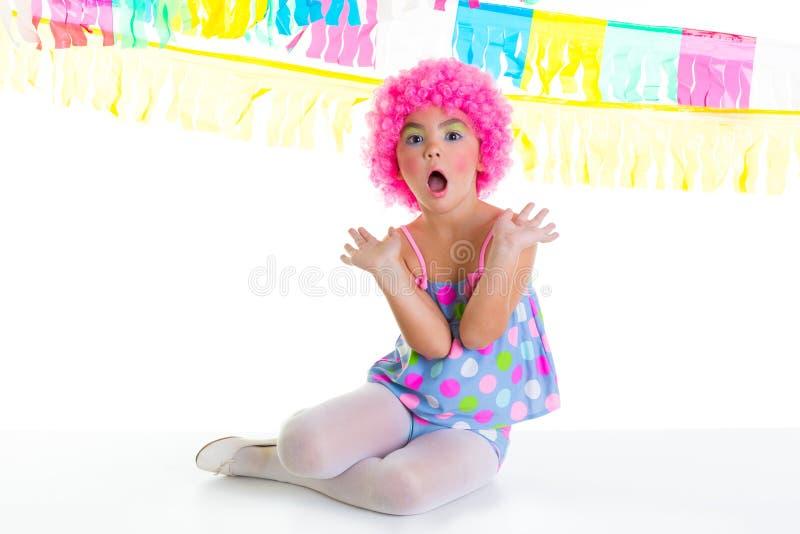 Het jonge geitjemeisje van het kind met roze de pruiken grappige uitdrukking van de partijclown stock afbeeldingen
