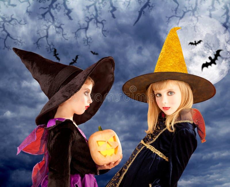 Het jonge geitjemeisjes en pompoen van Halloween in maanhemel royalty-vrije stock fotografie