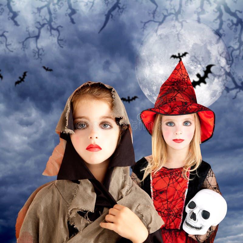 Het jonge geitjemeisjes van Halloween met schedel bewolkte maan stock afbeeldingen