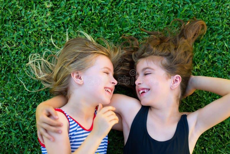 Het jonge geitjemeisjes van zusters glimlachen die op tuingras ligt stock fotografie