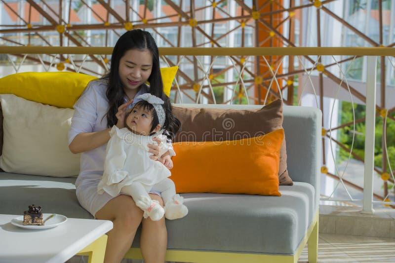 Het jonge gelukkige Aziatische Chinese vrouw spelen met de zitting van het babymeisje bij vakantietoevlucht die vakantie van reis stock afbeeldingen