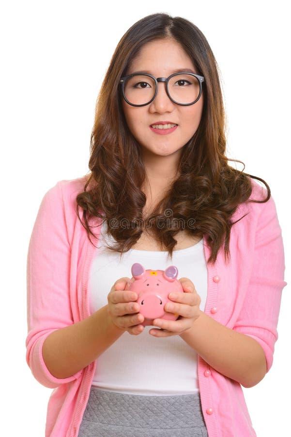 Het jonge gelukkige Aziatische spaarvarken van de vrouwenholding stock afbeelding