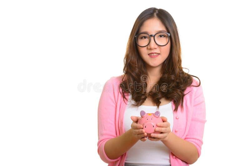 Het jonge gelukkige Aziatische spaarvarken van de vrouwenholding stock afbeeldingen
