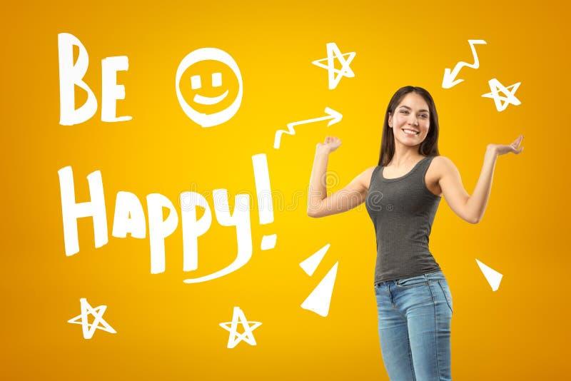 Het jonge gelukkige donkerbruine meisje die toevallige jeans en t-shirt dragen met IS GELUKKIGE teken en beeldverhaalsterren en s royalty-vrije stock afbeeldingen