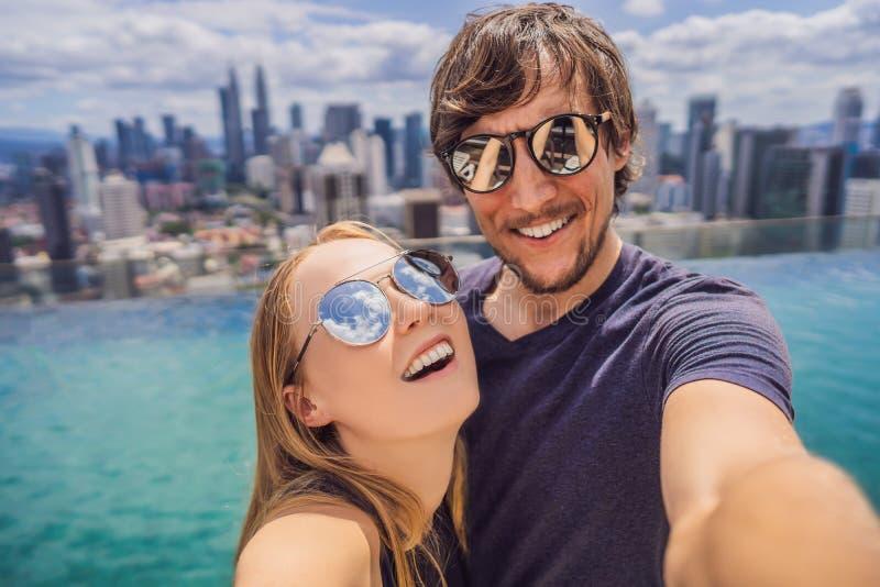 Het jonge gelukkige en aantrekkelijke speelse paar die selfie stelt bij luxe samen de stedelijke pool van de hoteloneindigheid ne stock foto's