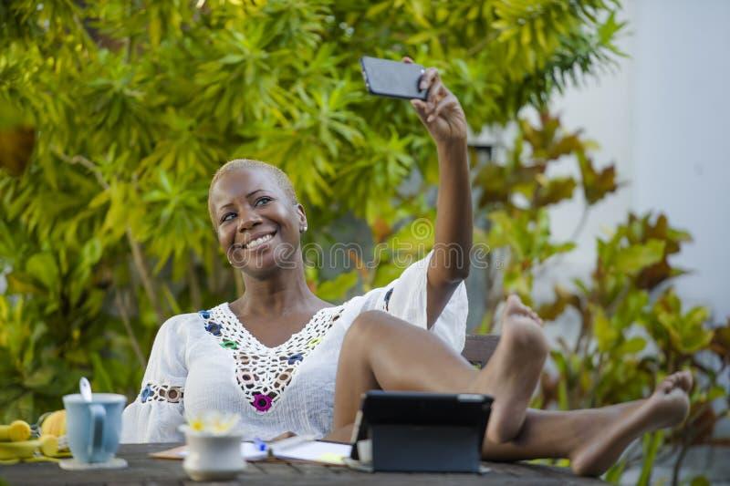 Het jonge gelukkige en aantrekkelijke zwarte afro Amerikaanse vrouw werken met digitale tablet in openlucht bij koffie die selfie stock afbeeldingen