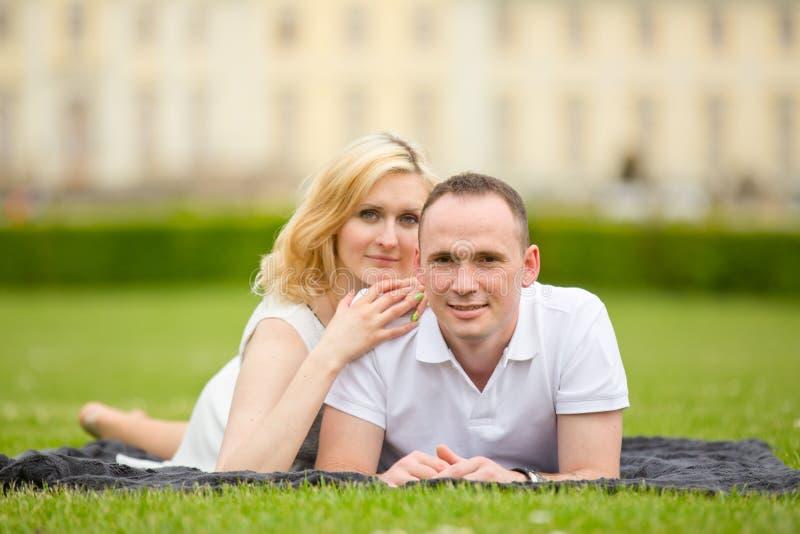 Het jonge, gelukkige en glimlachende paar ligt op een gras royalty-vrije stock foto's