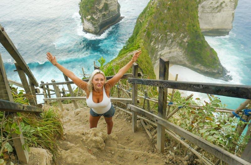 Het jonge gelukkige en mooie blonde vrouw glimlachen vrolijk bij het tropische landschap die van de strandklip onbezorgde van de  royalty-vrije stock fotografie
