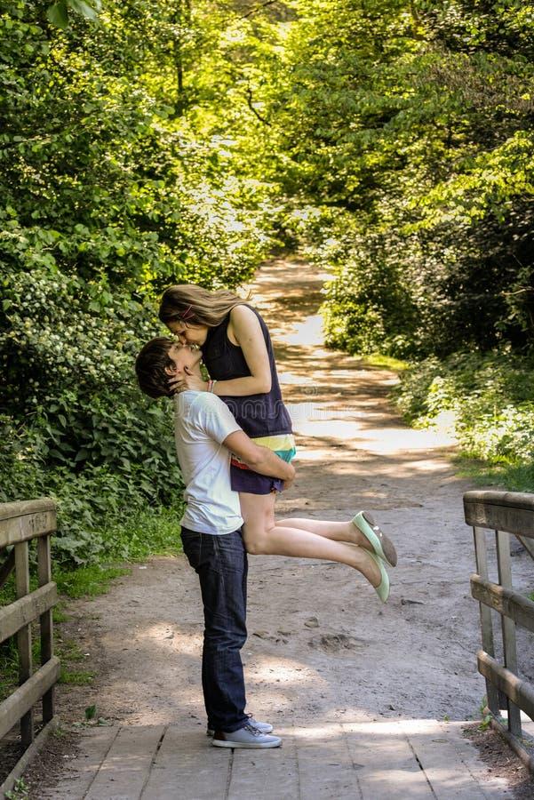 Het jonge gelukkige houdende van paar geniet van een ogenblik van geluk in bos royalty-vrije stock afbeelding
