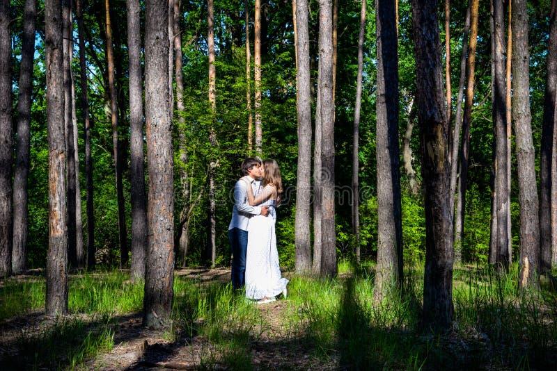 Het jonge gelukkige houdende van paar geniet van een ogenblik van geluk in bos royalty-vrije stock foto's