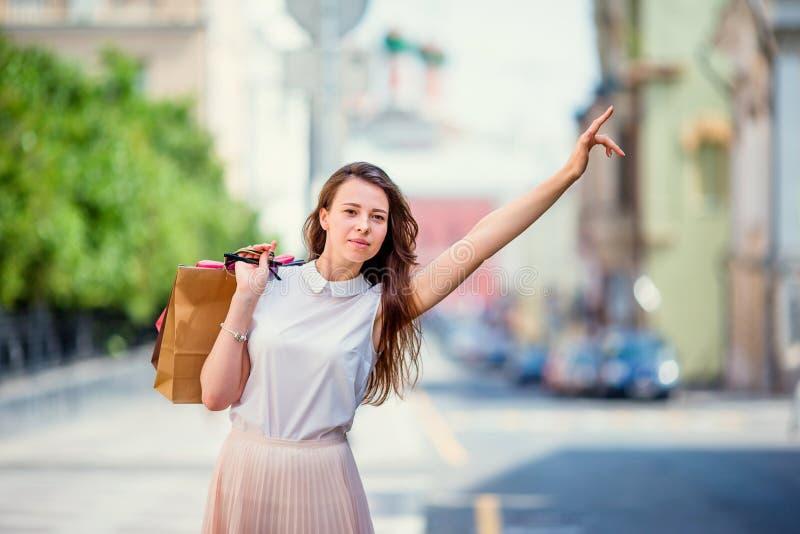 Het jonge gelukkige meisje met het winkelen zakken haalt een taxi Portret van een mooie gelukkige vrouw die zich op de straathold royalty-vrije stock afbeelding