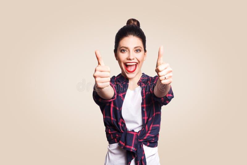 Het jonge gelukkige meisje met toevallig stijl en broodjeshaar beduimelt omhoog haar vinger, op beige blinde muur met exemplaar h stock foto's