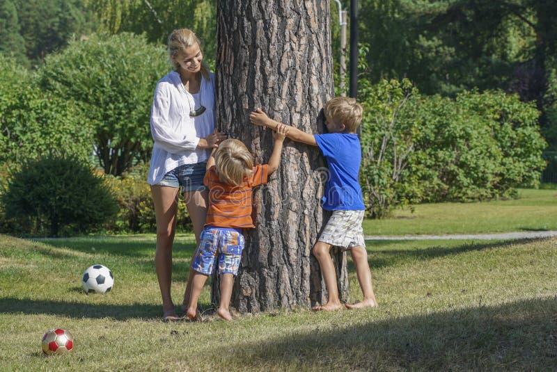 Het jonge gelukkige moeder spelen met twee jonge geitjes royalty-vrije stock afbeelding
