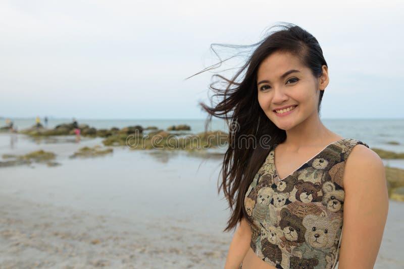 Het jonge gelukkige mooie Aziatische vrouw glimlachen bij het winderige publiek is stock foto's