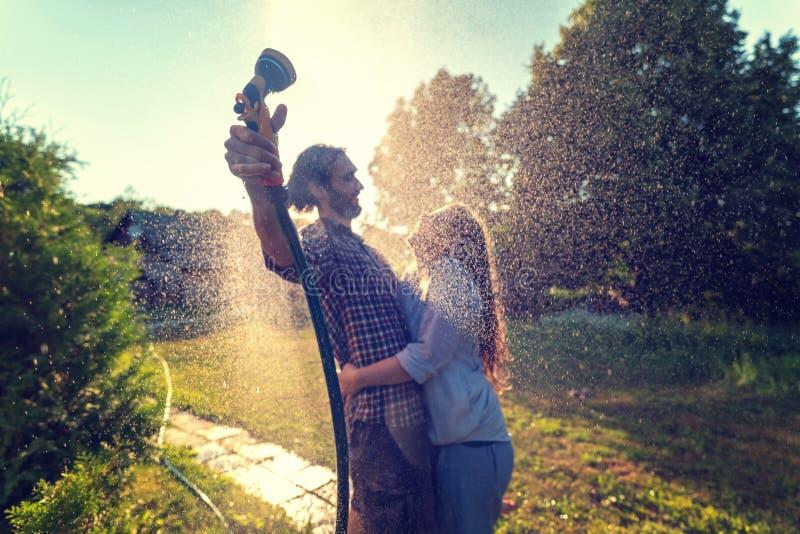 Het jonge gelukkige mooie paar hosing in de tuin, het de zomergeluk en het liefdeconcept royalty-vrije stock afbeeldingen