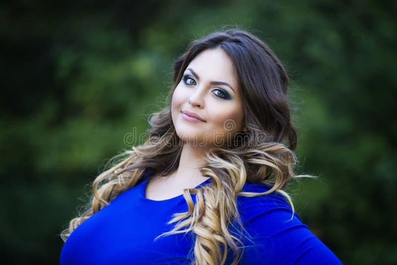 Het jonge gelukkige in openlucht glimlachen plus groottemodel in blauwe kleding, xxl vrouw op aard, professioneel make-up en kaps royalty-vrije stock afbeeldingen