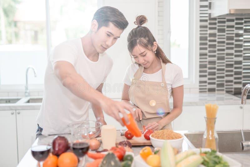 Het jonge gelukkige paar koken samen in de keuken thuis stock foto