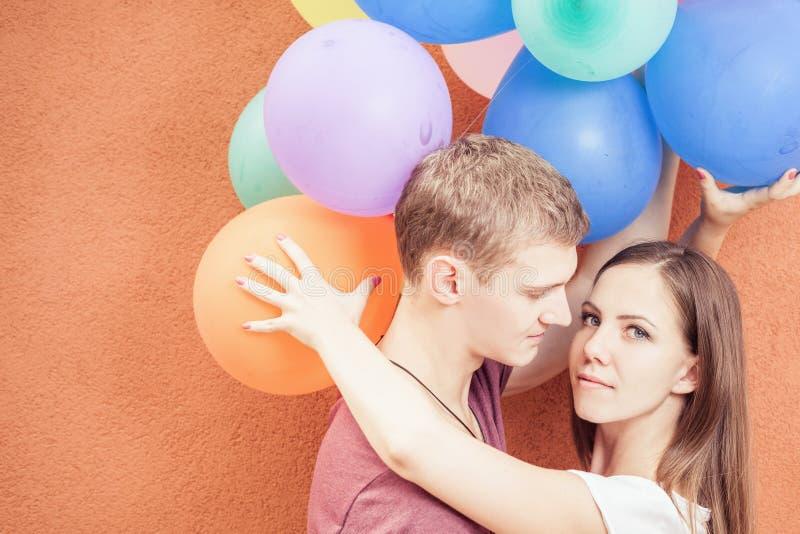 Het jonge gelukkige paar kussen dichtbij oranje muurtribune met ballons stock fotografie