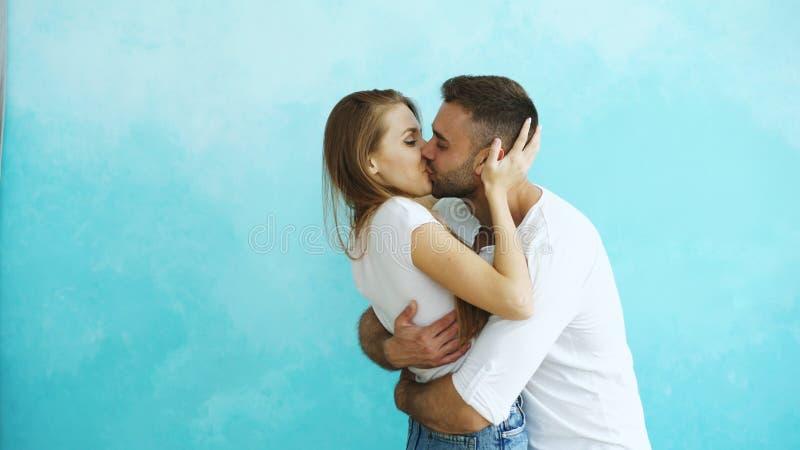 Het jonge gelukkige paar kussen op blauwe achtergrond royalty-vrije stock foto