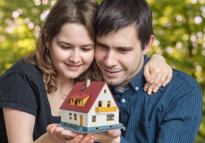 Het jonge gelukkige paar in liefde droomt en plant een nieuw huis stock afbeelding