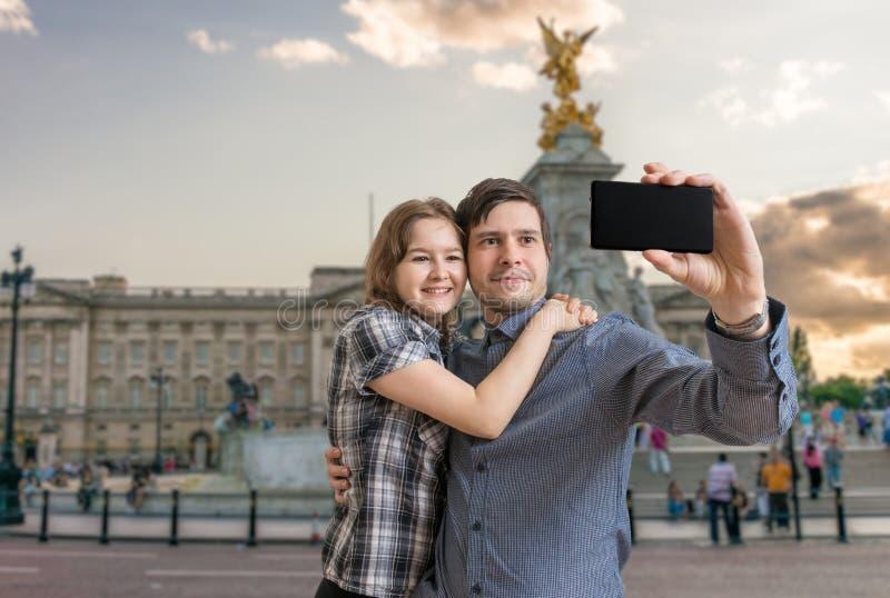 Het jonge gelukkige paar neemt selfie foto dichtbij Buckingham-paleis royalty-vrije stock foto