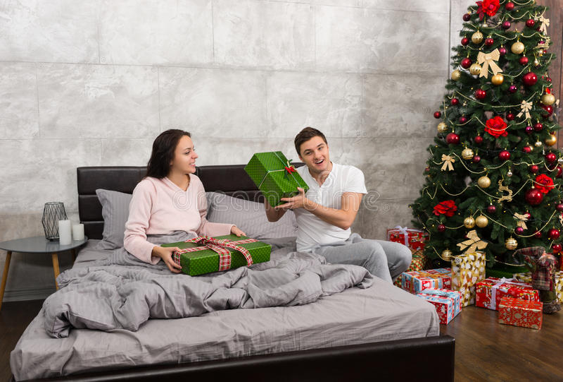 Het jonge gelukkige paar in pyjama's verheugt zich bij hun voorstelt terwijl Si stock afbeeldingen
