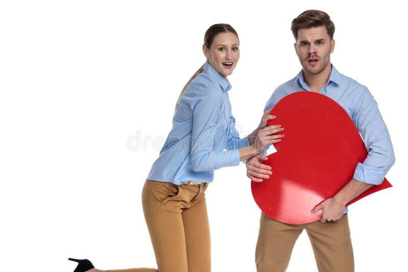 Het jonge gelukkige paar spelen met een groot rood hart stock afbeeldingen
