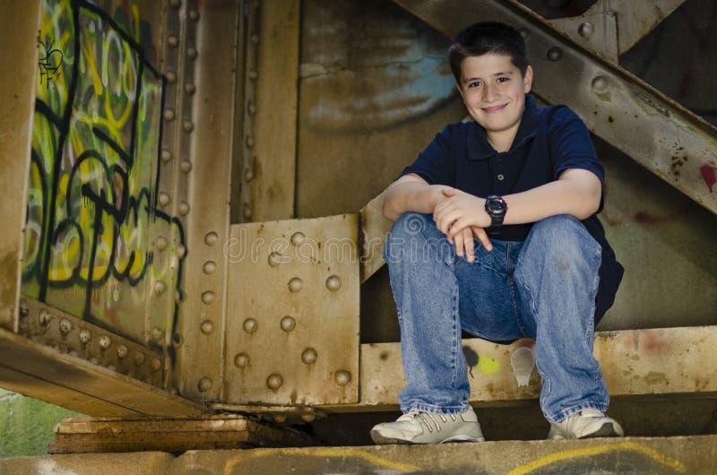 Het jonge gelukkige pre-tiener stellen bij de brug van de treinschraag royalty-vrije stock foto's