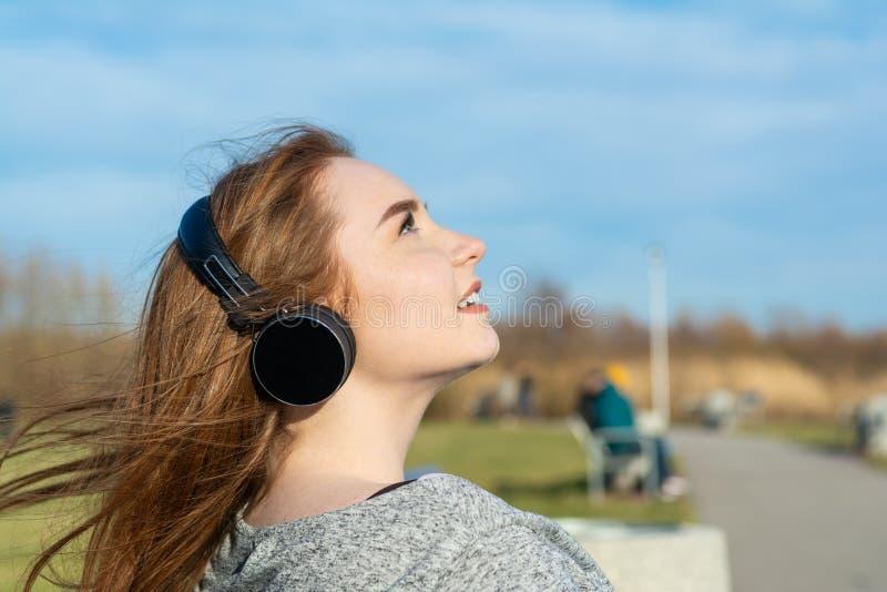 Het jonge, gelukkige roodharigemeisje in de lente in het park dichtbij de rivier luistert aan muziek door draadloze bluetoothhoof royalty-vrije stock afbeelding