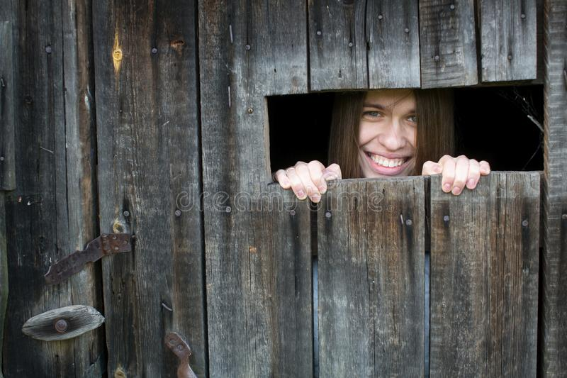Het jonge gelukkige vrouw glimlachen die uit het venster in een houten loods kijken royalty-vrije stock foto's
