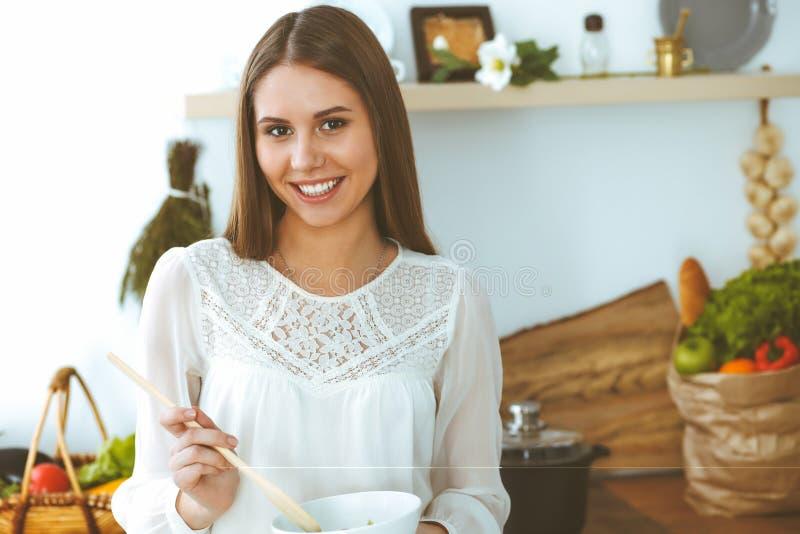 Het jonge gelukkige vrouw koken in de keuken Gezonde maaltijd, levensstijl en culinaire concepten De goedemorgen begint met vers royalty-vrije stock afbeeldingen