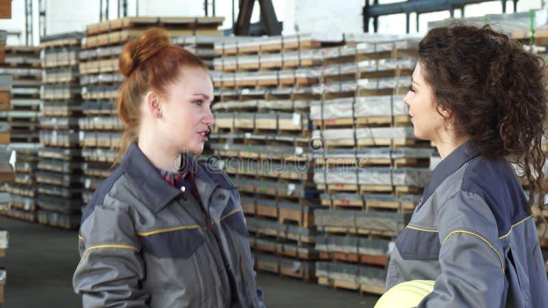 Het jonge gelukkige vrouwelijke fabrieksarbeiders hoge fiving bij het pakhuis stock fotografie