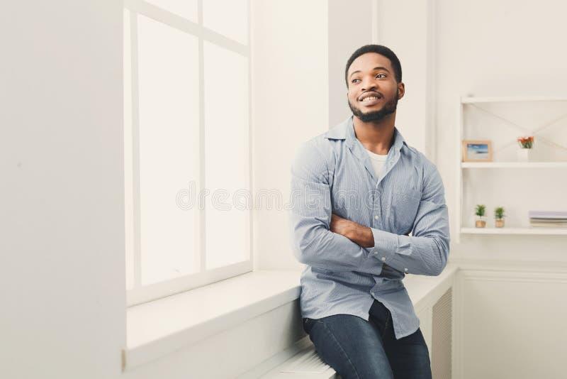 Het jonge gelukkige zwarte mens stellen bij venster royalty-vrije stock foto