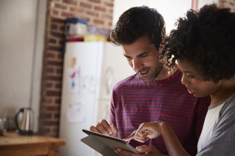 Het jonge gemengde raspaar die tablet in keuken bestuderen, sluit omhoog royalty-vrije stock foto's